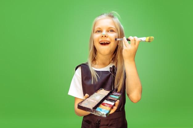 Provando. bambina che sogna la professione di truccatore. infanzia, pianificazione, educazione e concetto di sogno. vuole diventare impiegato di successo nel settore della moda e dello stile, artista di acconciature.
