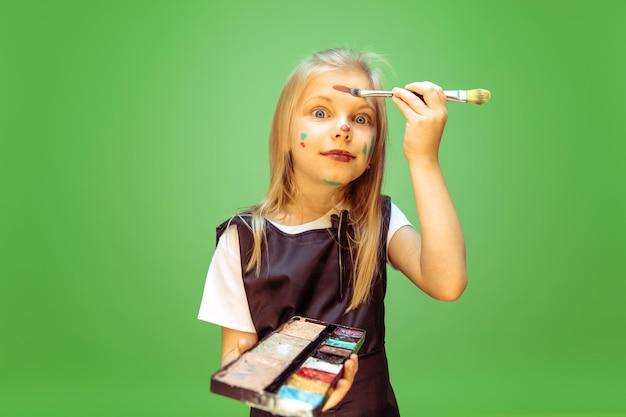 Пробуем. маленькая девочка мечтает о профессии визажиста. детство, планирование, образование и концепция мечты.