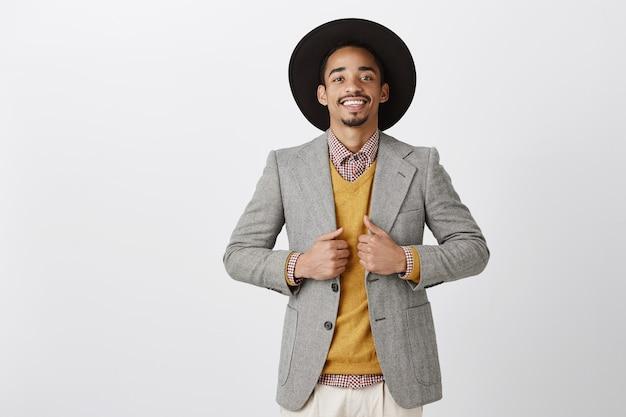 Примерить новый стиль, купить в магазине модную куртку. портрет счастливого успешного темнокожего бородатого мужчины в черной шляпе, довольного и уверенно стоящего над серой стеной, удовлетворенно улыбающегося