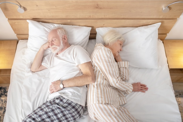 Trying to sleep. aged married couple lying in bed back to back
