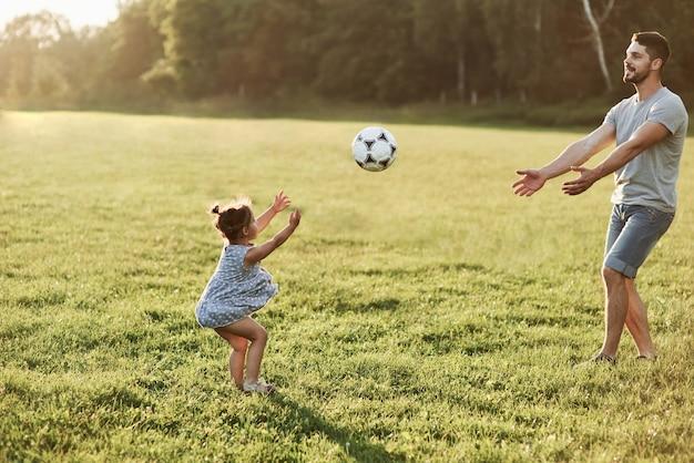 キャッチしようとしています。娘が背景の美しい草や森にボールを投げているお父さんの写真。