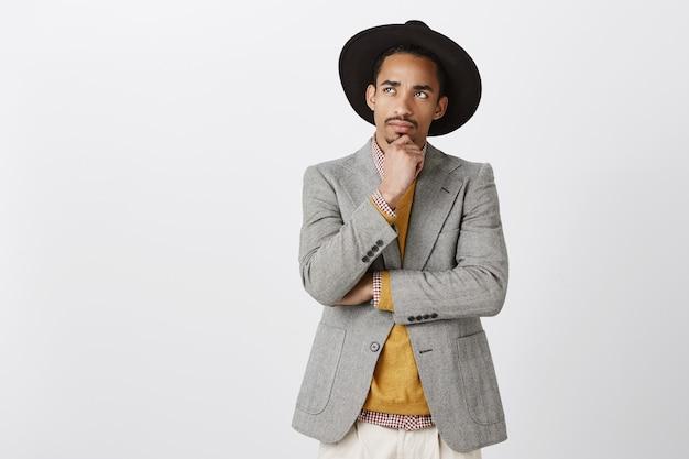 解決策を見つけようとして、人生をより良いものにします。スタイリッシュな衣装と黒い帽子の魅力的なアフリカの男性に焦点を当て、あごに触れ、思慮深い表情で見上げる、重要なイベントを考える、または思い出す