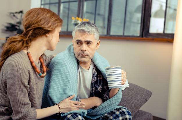 暖かくしようとしています。暖かくしようとしている間熱いお茶のカップと一緒に座っている元気のない悲しい男