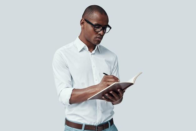 Пытаюсь все отмечать. красивый молодой африканский человек что-то записывает, стоя на сером фоне