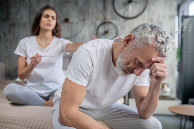 말하려고합니다. 불행한 회색 머리 수염 난 남편이 앉아서 그의 어깨를 만지는 아내