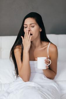 Пытаюсь проснуться. молодая женщина, зевая и держа чашку, сидя в постели у себя дома