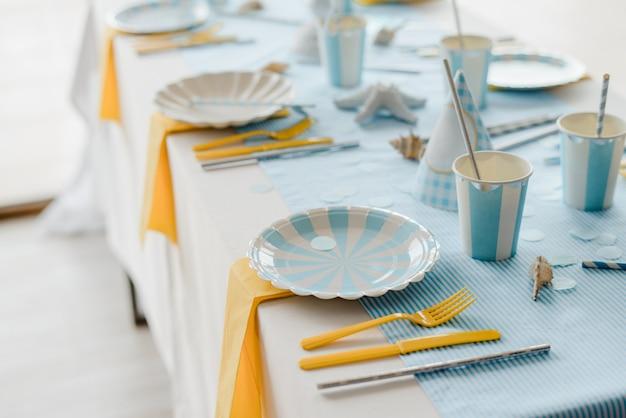 スカイブルーと白の色で子供や女の子のパーティーのために準備された誕生日テーブルの紙皿。男の子のシャワー。クローズアップ、tselectiveフォーカス