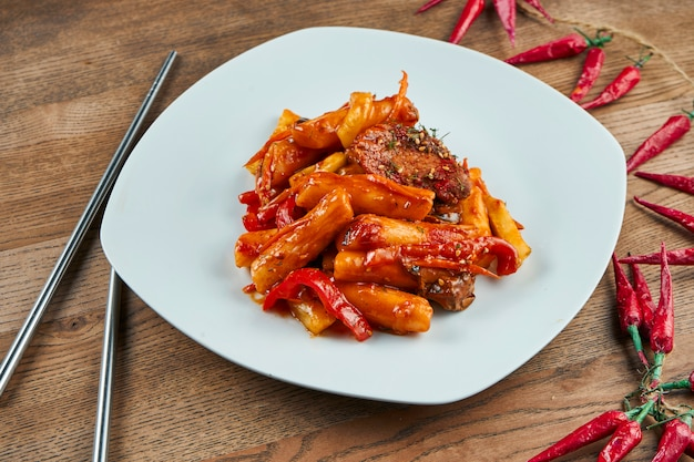 Tteok-bokki - традиционное блюдо корейской кухни, жареные рисовые лепешки со свиными ребрышками в белой тарелке на дереве. закройте выборочный фокус