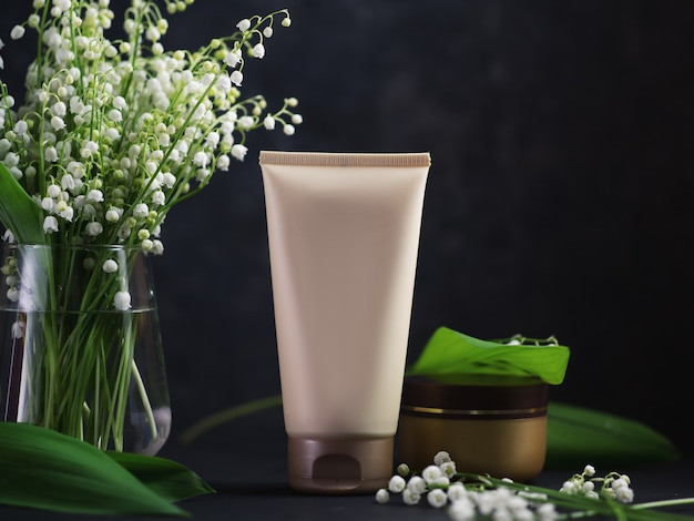 A tube of face and skin cream on a black table with a bouquet of lilies of the valley flowers