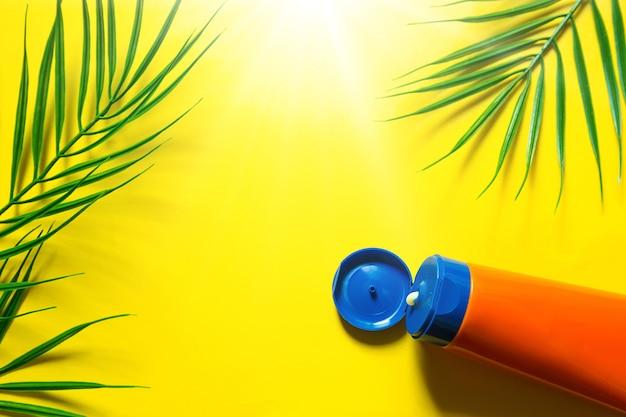 Тюбик солнцезащитного крема на желтом летнем фоне с пальмовыми листьями и солнцем. средство для загара, защита кожи, поездка на море, отдых на пляже, уф-защита, spf фильтр. плоская планировка, копия пространства