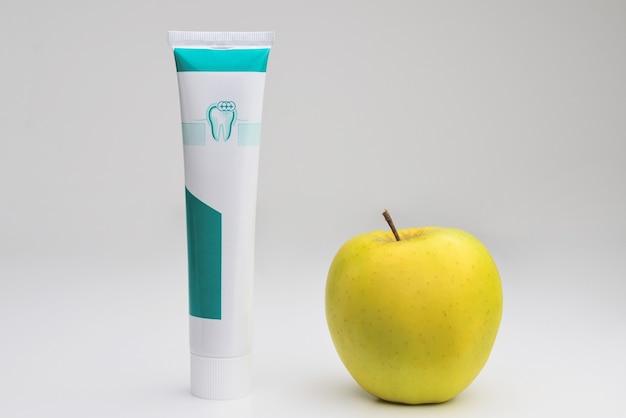 Тюбик зубной пасты и зеленого яблока на белом фоне