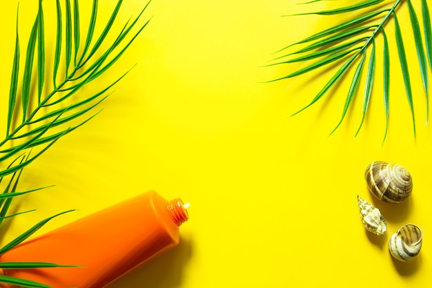 Tube of sunscreen on a yellow summer background with palm leaves and the sun. tanning agent, skin protection, a trip to the sea, vacation on the beach, uv protection, spf filter. flat lay, copy space