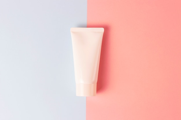 Tube with cream on a blue and pink background, front view, cosmetics care concept