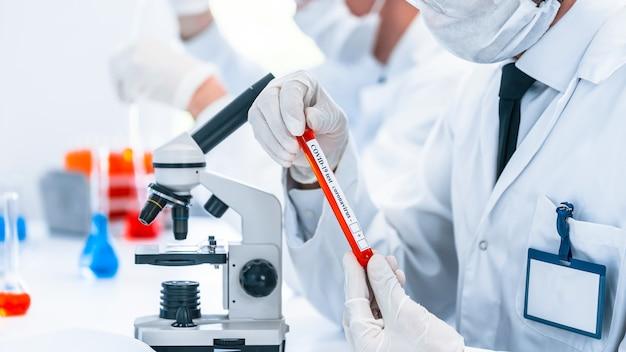 Трубка с тестом на коронавирус в руках ученого. фото с копией пространства.