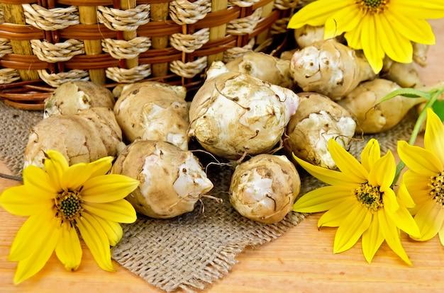 예루살렘 아티 초크의 괴경과 노란 꽃, 삼베 천과 나무 보드의 배경에 바구니