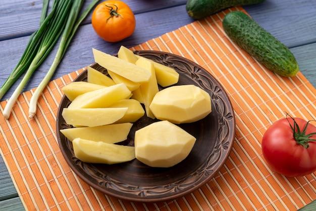 껍질을 벗긴 생 감자의 괴경은 야채와 함께 식탁에 있는 접시에 있습니다. 요리를 위한 준비.