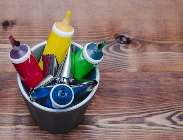 Tubes of colored paint on wooden background
