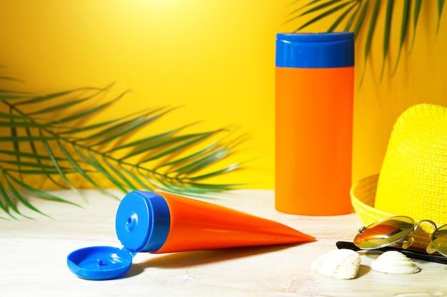 Трубки с мокапами солнцезащитных кремов на столе с желтым летним фоном. защита кожи от ультрафиолета с помощью spf-фильтра, шампуня для ухода за волосами и кондиционера. безопасный загар на пляже, курорт на море.