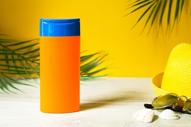 Tubes with mock up sunscreens on the table with yellow summer background. uv protection of the skin with an spf filter, hair care-shampoo and conditioner. a safe tan on the beach, resort on the sea.