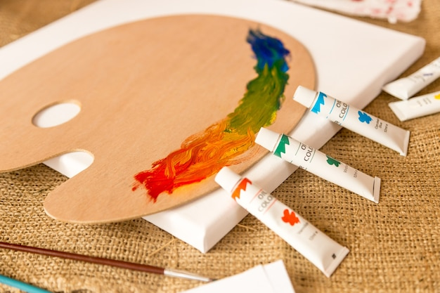 キャンバスに油絵の具が置かれたチューブと、異なる色のパレット