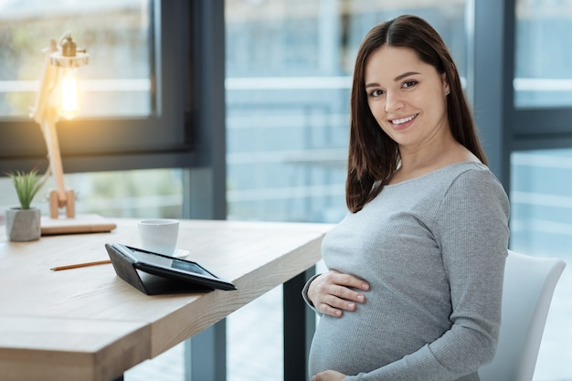 Tue beauty. close up of gracious pregnant woman looking at you with a smile while sitting at the table and touching her stomach