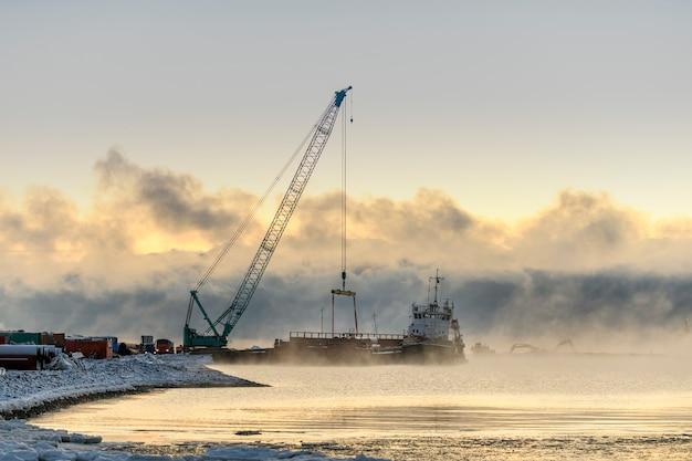 Буксир пришвартован к барде. сильный туман в арктическом море. строительство морские морские работы. строительство плотины, кран, баржа, земснаряд.