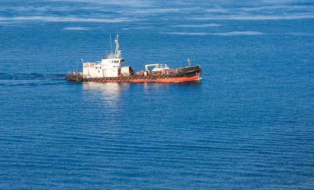 Буксируйте корабль в солнечный осенний день на синем море