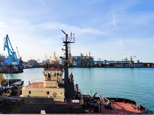 항구의 부두에서 예인선 지원, 바다 위의화물 항구, 떠 다니는화물 크레인