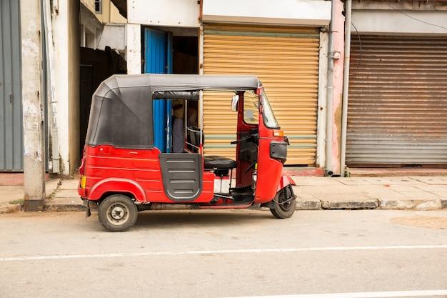 Tuk-tuk on road of sri lanka, side view. ceylon traditional tourist transport, local taxi