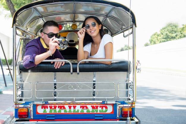 Молодая пара туристов, путешествующих на местном такси tuk tuk в бангкоке, таиланд