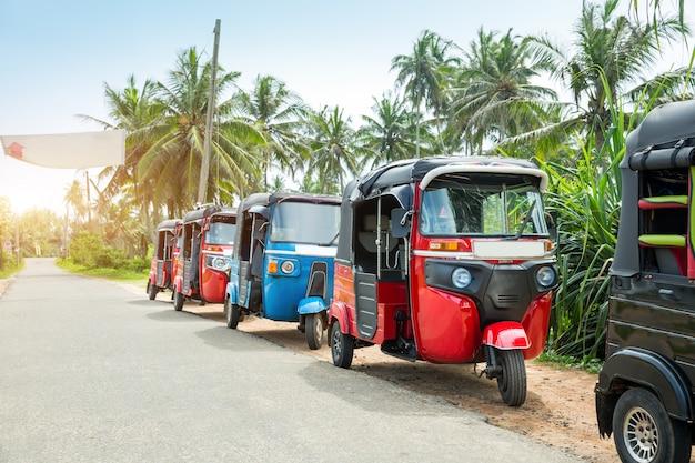 スリランカ、セイロンの旅行車の道のトゥクトゥクタクシー。セイロン熱帯林と伝統的な観光輸送