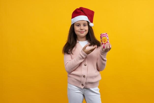 トゥーラ、ロシア-2021年8月23日:チュッパチャプスの瓶を持ったサンタのクリスマスキャップの少女が黄色の背景に彼女の手で飲む