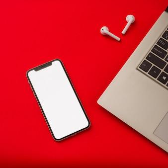 툴라, 러시아-2019 년 5 월 24 일 : 노트북과 빨간색 배경에 apple iphone x 및 airpods. 스마트 폰의 화면이 흰색입니다. 목업.
