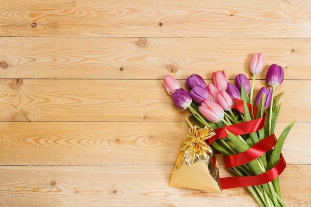Букет тюльпанов с красной лентой и подарком в сумке gloden на натуральной деревянной текстуре