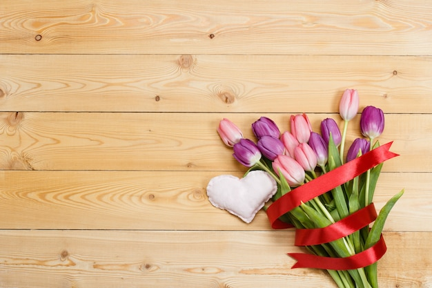 Tulip bouquet with red ribbon and fabric handmade heart on natural wooden texture