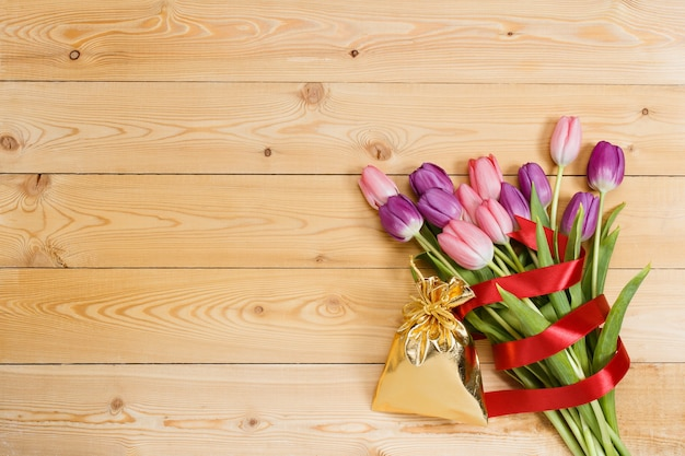 Tulip bouquet with red ribbon and gift in gloden bag on natural wooden texture
