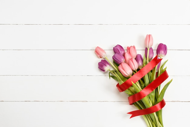 Tulip bouquet with red ribbon on white wooden background with copy space