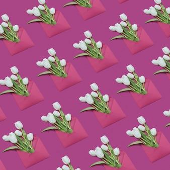 マゼンタの背景に手作りの封筒のパターンのチューリップの花束。おめでとうございます。フラットレイ。