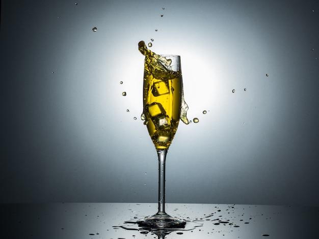 Tulip champagn glass、ざらつきのある反射で黄色い水で氷結する