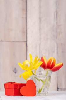 하트 인사와 함께 유리 꽃병에 튤립 꽃꽂이, 나무 테이블 배경 벽에 물을 수 있는 장식, 클로즈업, 어머니의 날 디자인 개념.