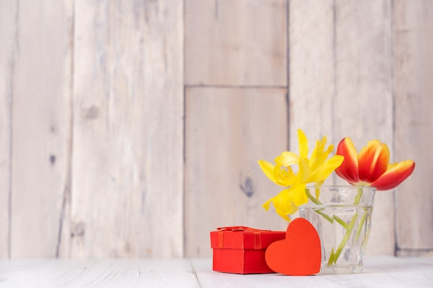 ハートの挨拶とガラスの花瓶のチューリップのフラワーアレンジメント、木製のテーブルの背景の壁にじょうろの装飾、クローズアップ、母の日のデザインコンセプト。