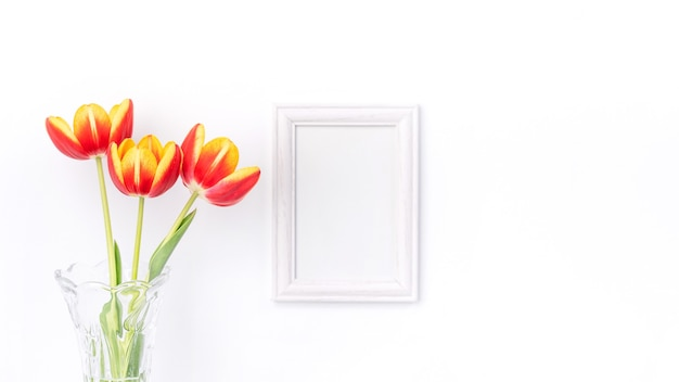 Tulip flower in glass vase with picture frame on white wall, mother's day decor concept.