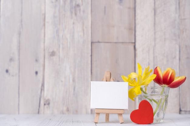 집에 있는 나무 테이블 배경 벽에 그림 프레임 장식이 있는 유리 꽃병에 튤립 꽃, 클로즈업, 어머니의 날 디자인 개념.