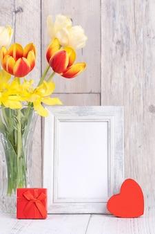 自宅の木製テーブルの背景の壁に額縁の装飾が施されたガラスの花瓶のチューリップの花、クローズアップ、母の日のデザインコンセプト。