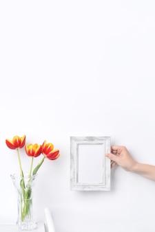 自宅のきれいな壁に対して白い木製のテーブルの背景に額縁の場所とガラスの花瓶のチューリップの花、クローズアップ、母の日の装飾のコンセプト。