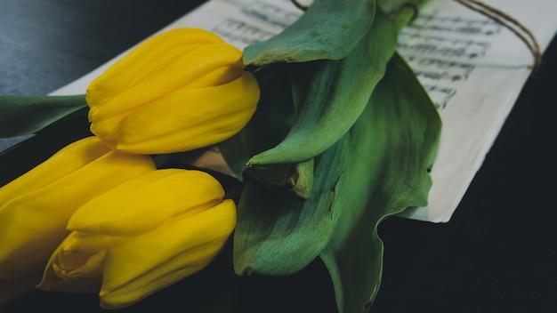 Dlack 배경에 오래 된 음표의 시트에 튤립 꽃. 노란 튤립입니다.