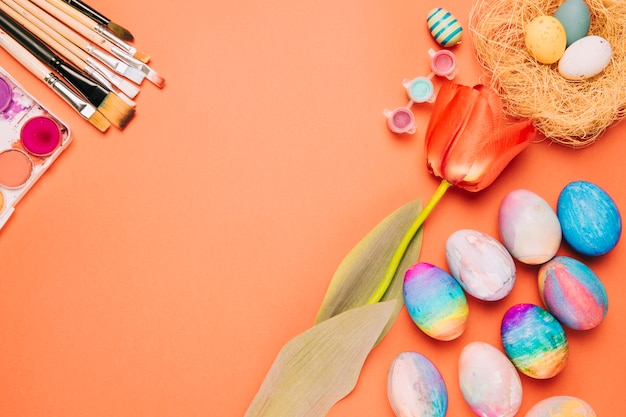Tulip flower; paintbrushes; colorful easter eggs and nest on an orange background