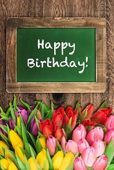 チューリップの花とヴィンテージの緑の黒板。サンプルテキストお誕生日おめでとう!