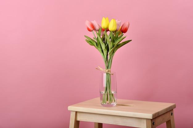 튤립 꽃 꽃다발. 나무 테이블에 꽃병에 인공 튤립 배열입니다.