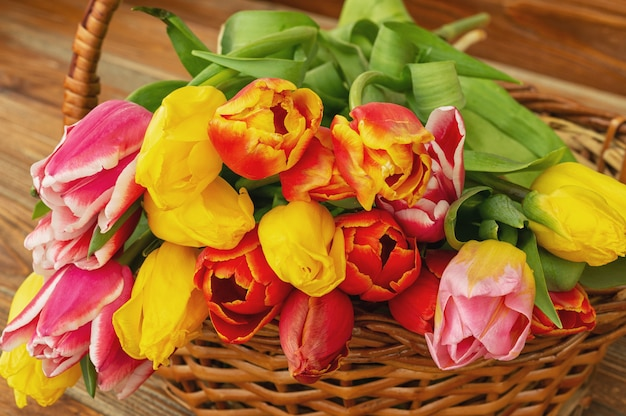 Tulip flowers bouquet in a basket,on brown table, outdoor.